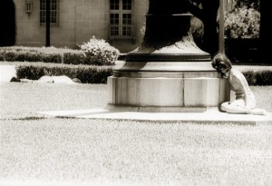 A woman cowers behind the base of a flagpole at the University of Texas at Austin on Aug. 1, 1966